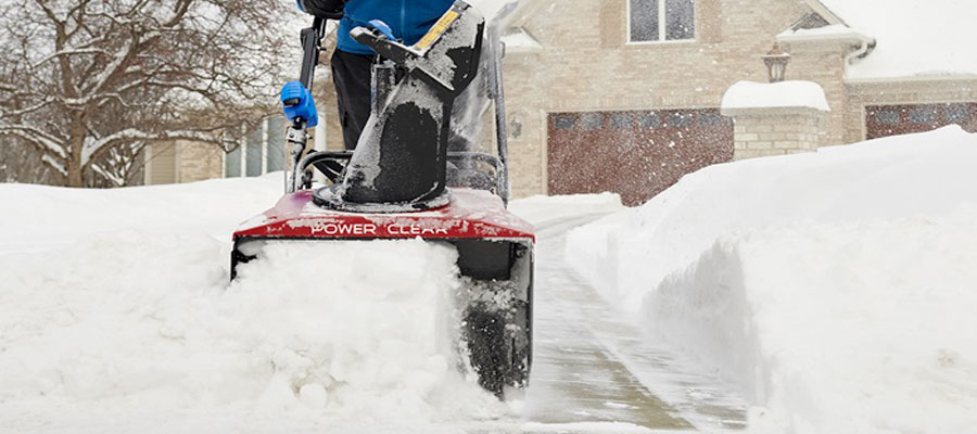 Snow blower clearing a driveway from Pickering Mower