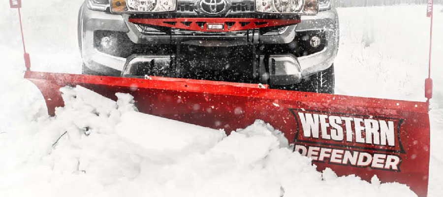 Western Snow Plow available at Pickering Mower clearing a road
